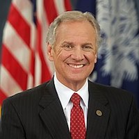 Governor Henry McMaster smiling in front of an American flag and the South Carolina state flag