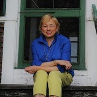 Maine Governor Janet Mills smiling, sitting on steps outside a house