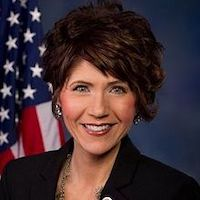 South Dakota Governor Kristi Noem smiling in front of an American flag