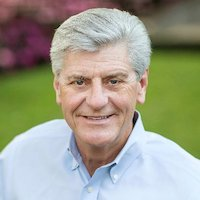 Mississippi Governor Phil Bryant smiling in front of a blurred outdoor background