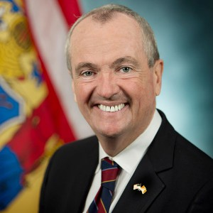 New Jersey Governor Phil Murphy wearing a suit, smiling in front of a blurred background of a flag