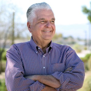 Nevada Governor Steve Sisolak smiles looking off camera in front of a blurred background of trees and mountains