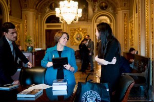 Amy Klobuchar working in Congress with staffers on legislation