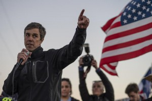 Beto O'Rourke speaks to a crowd with a U.S. flag flying in the background.