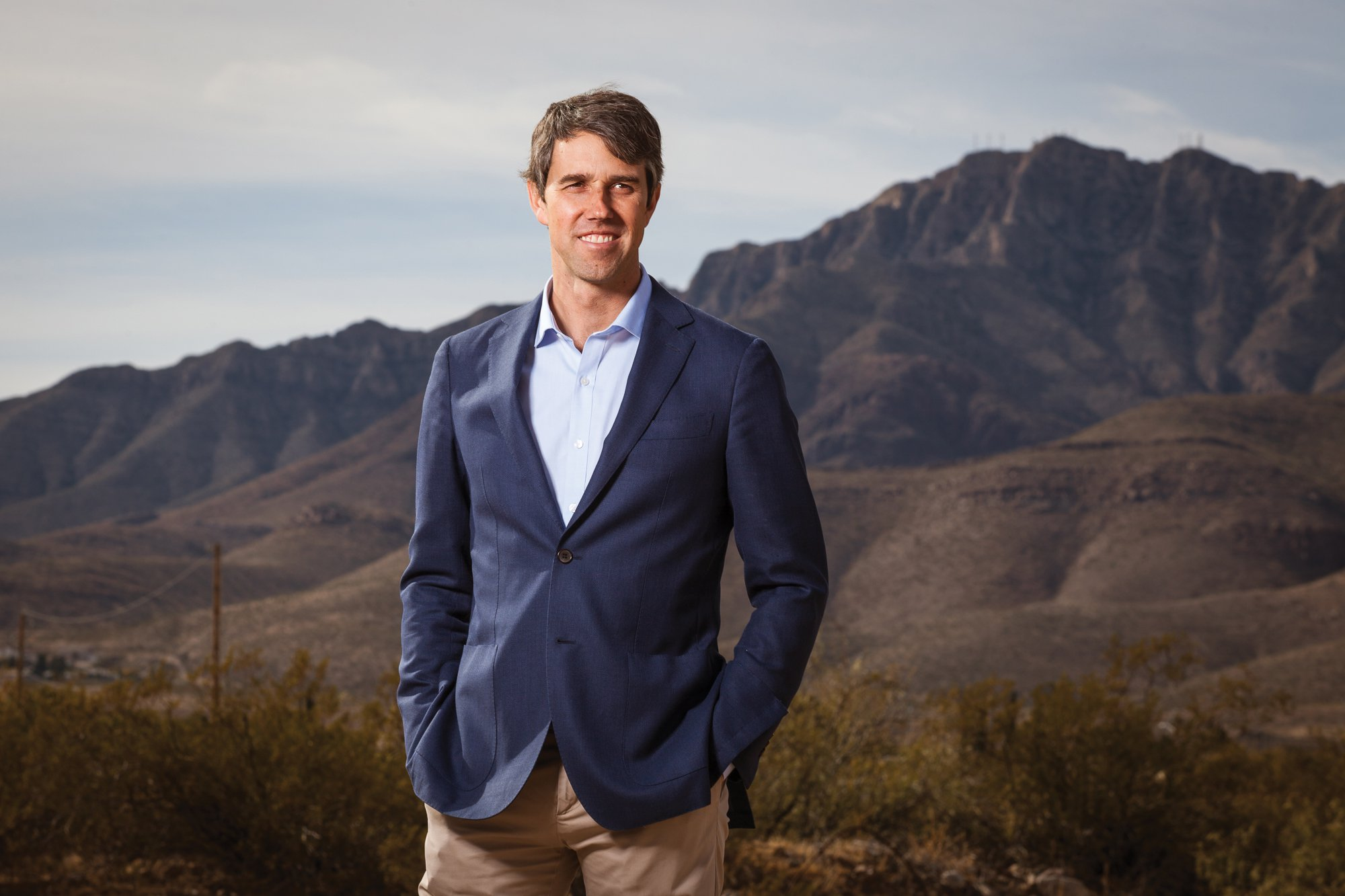 Beto O'Rourke stands in front of a mountainous background with his hands in his pockets, smiling.