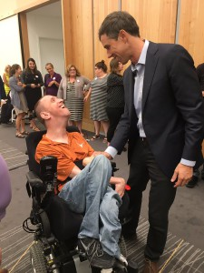 Beto O'Rourke speaks to a caucasian man in a power wheelchair