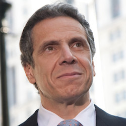 Governor Andrew Cuomo smiling in front of a blurred background of buildings