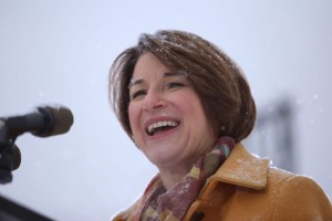 Amy Klobuchar speaks into a microphone amidst a blizzard