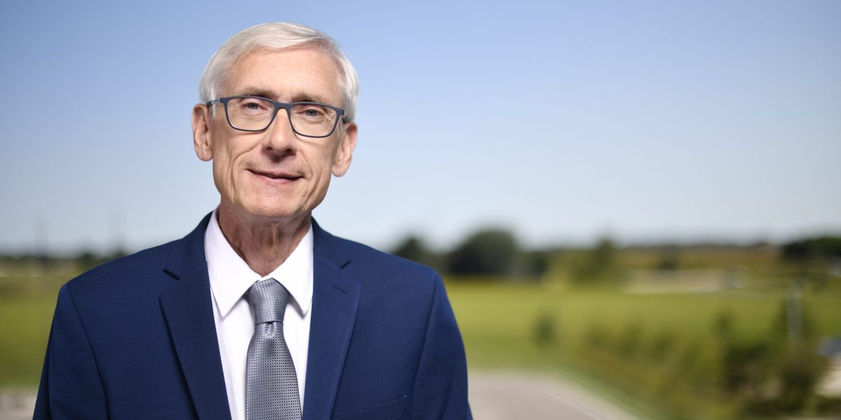 Governor Tony Evers smiling in front of a blurred background of grass, trees, and road