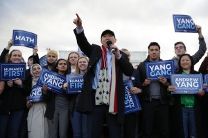 Yang talks into a microphone with his arm outstretched  with fans behind him holding signs