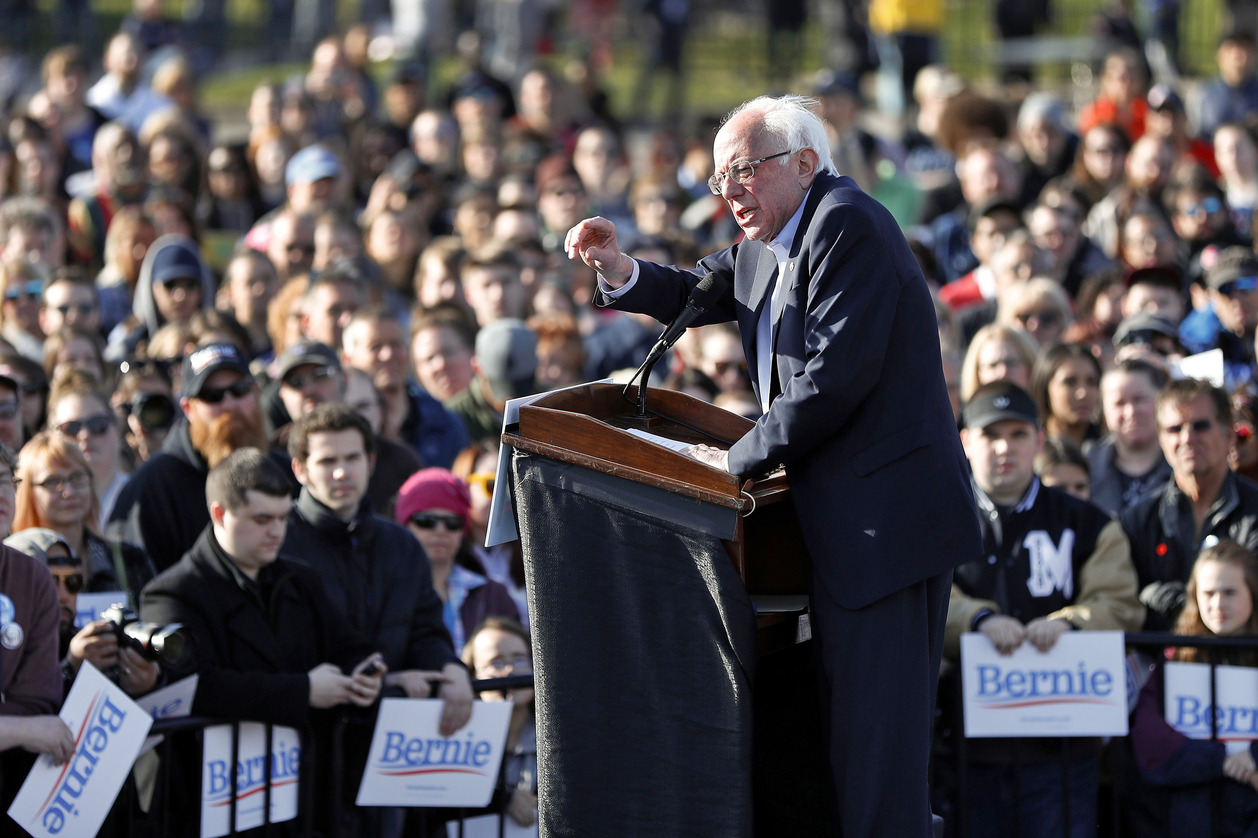 Bernie Sanders speaking behind a podium at a rally