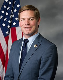 Swalwell smiles for the camera in front of the U.S. flag