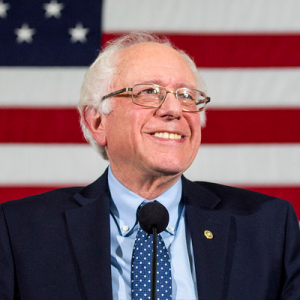 Bernie Sanders smiling in front of an American flag