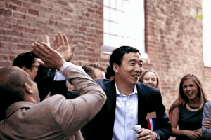 Yang smiles as he's surrounded by supporters