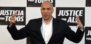 "Booker smiles with his arms outstretched in front of campaign signs that read, ""Equal Justice for All"" in English and Spanish."