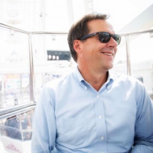 Steve Bullock wearing sunglasses and a blue button down shirt, smiling and looking to his lef