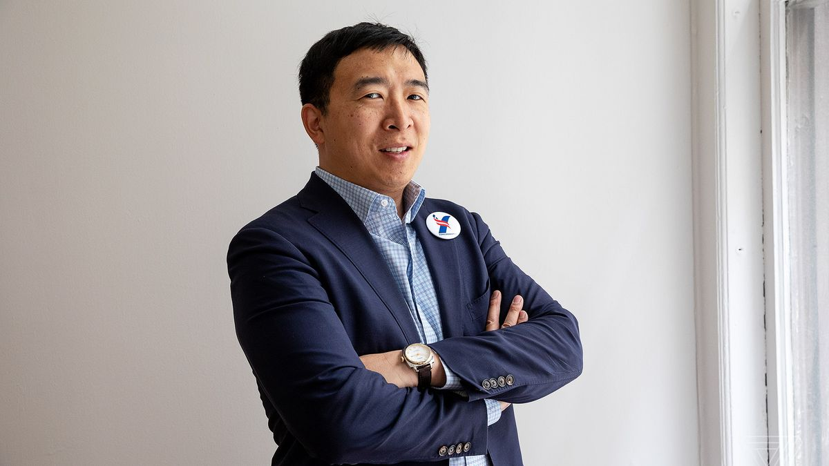 Yang poses for the camera with his arms folded and campaign button affixed to his jacket