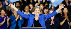 Warren waves with both arms to a crowd of supporters