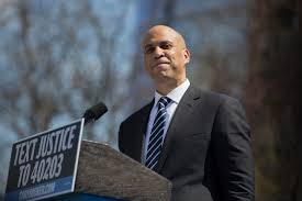 Booker stands behind a podium at a presidential campaign rally