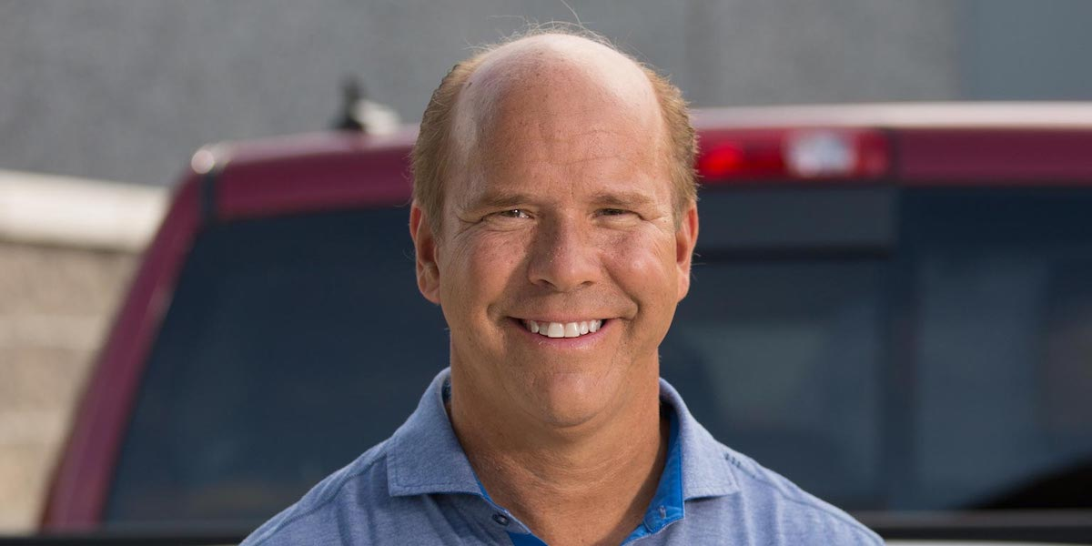 John Delaney smiling in front of a truck