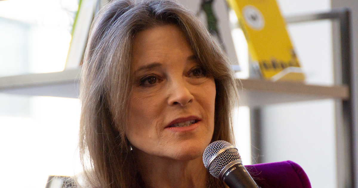 Marianne Williamson holding a microphone, speaking in front of a bookshelf in front of a window