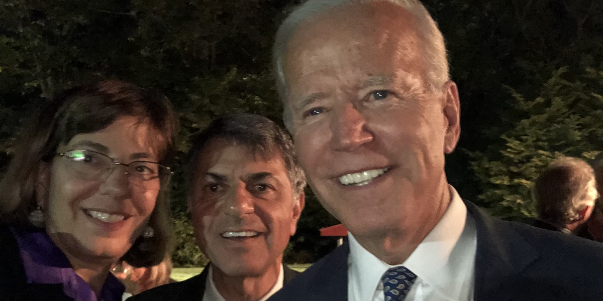 Jennifer Mizrahi and Joe Biden smile in front of trees and other guests outside at night
