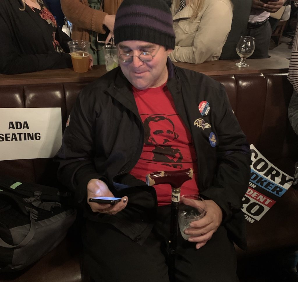 David P. using his phone in the ADA Seating section at the Cory Booker fundraiser in Washington DC
