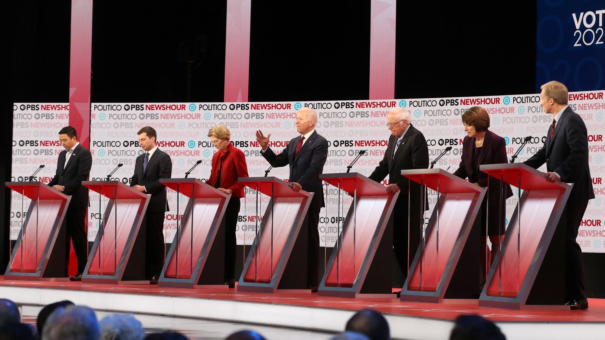 seven candidates standing behind podiums at the PBS / Politico debate