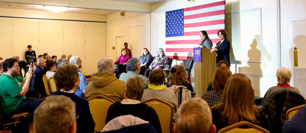four individuals, one being Sen. Amy Klobuchar, seated on a stage, while other people are in the audience
