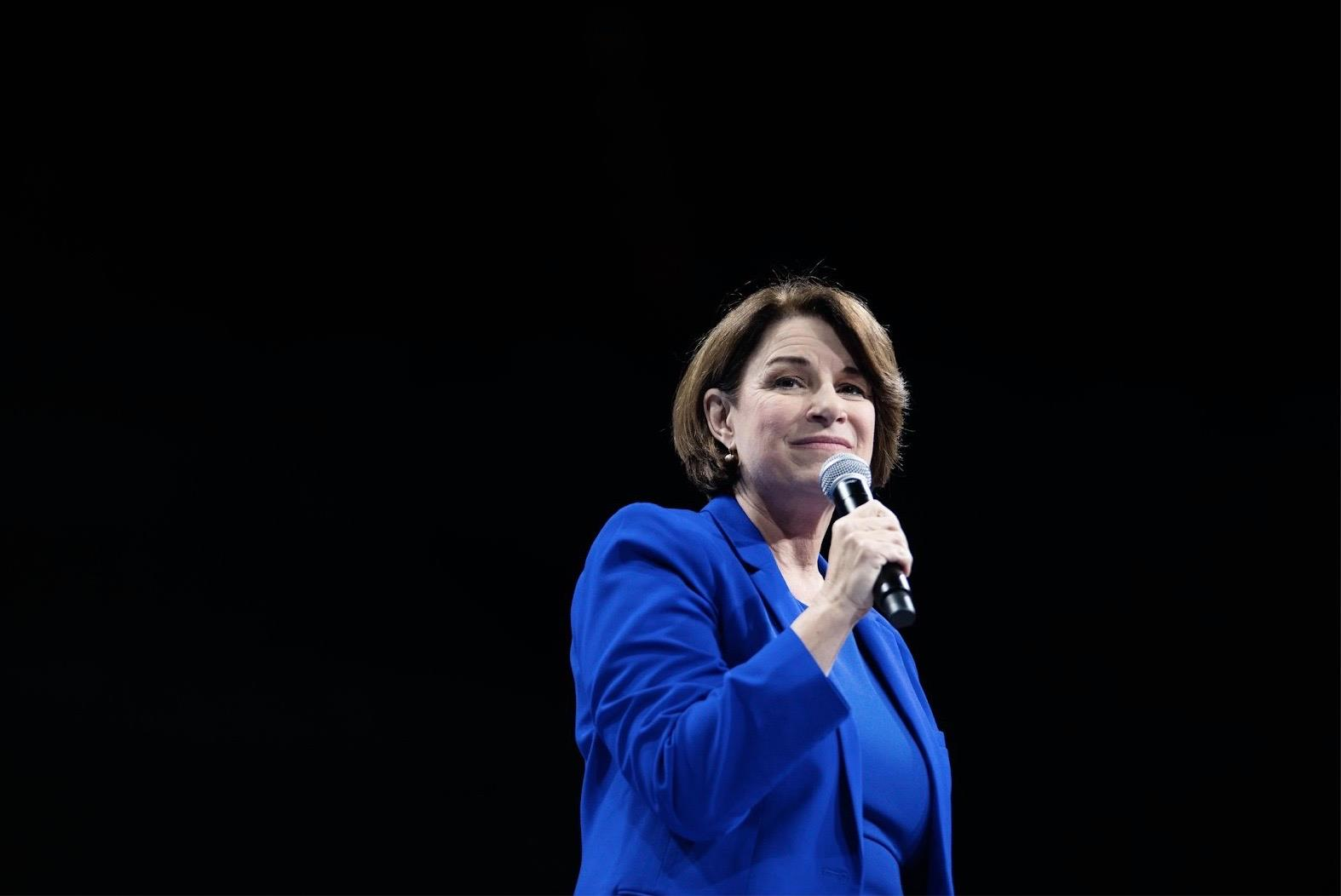 amy klobuchar wearing a blue suit standing against a black backdrop, holding a microphone and speaking