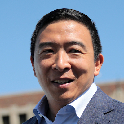 close up of Andrew Yang smiling wearing a white collared shirt and gray suit jacket