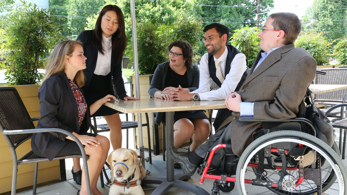 Five people with disabilities sitting around a picnic table having a conversation