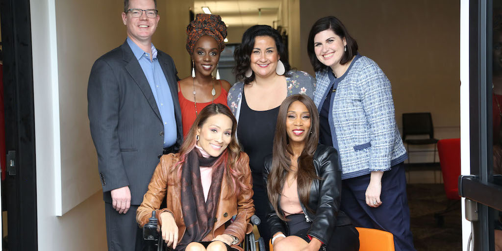 Six diverse people with disabilities smile together inside of a hallway