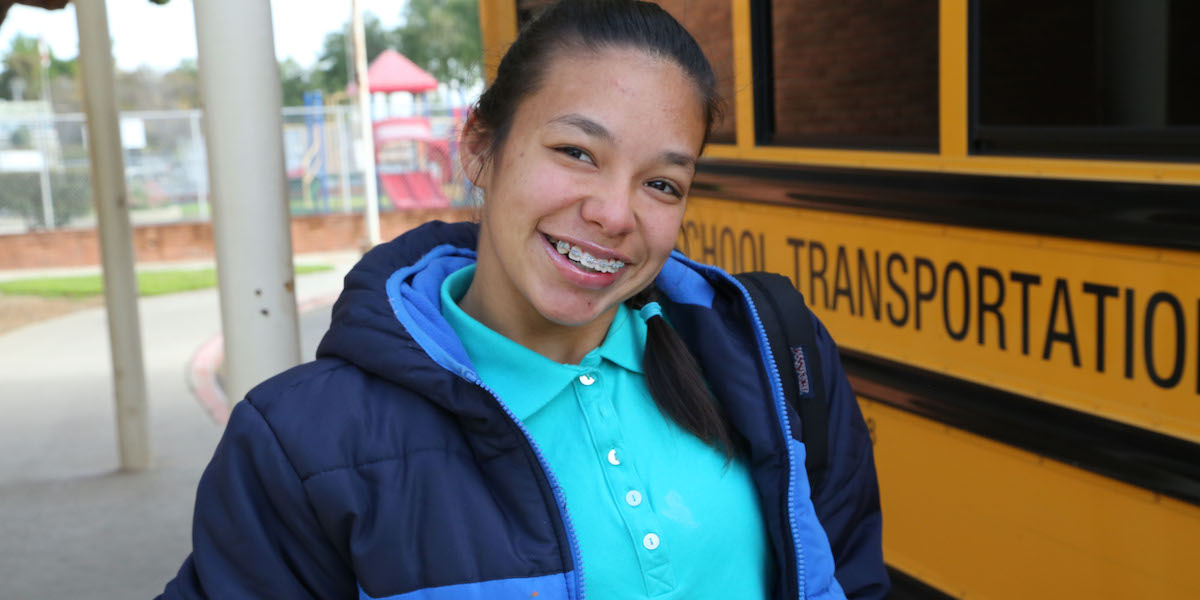 A young woman with a disability smiling in front of a school bus.