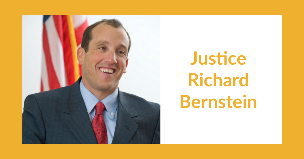 Headshot of Justice Richard Bernstein smiling in front of an American flag. Text: Justice Richard Bernstein