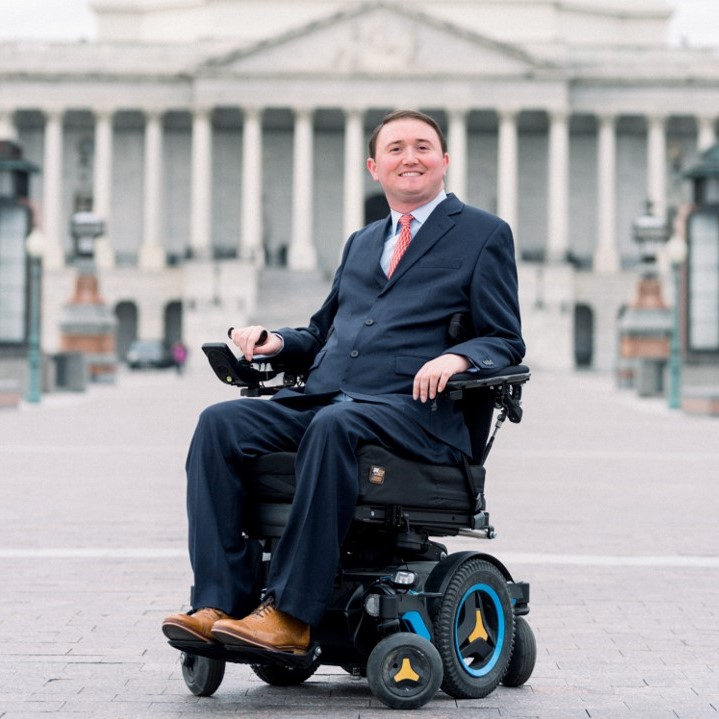 Josh Basile smiling, sitting in his power wheelchair with the US Capitol behind him.