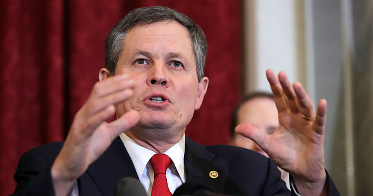 Steve Daines speaking wearing a suit and tie
