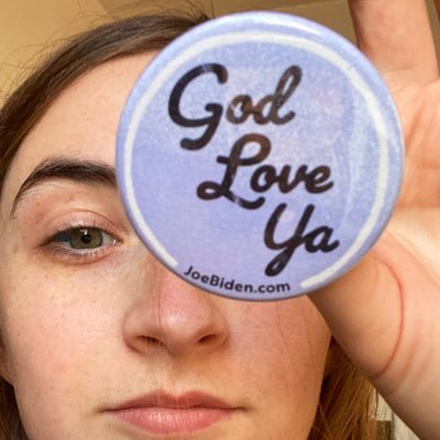 "Molly Doris-Pierce holding a button from the Biden campaign that says ""God Love ya"" and JoeBiden.com on it."