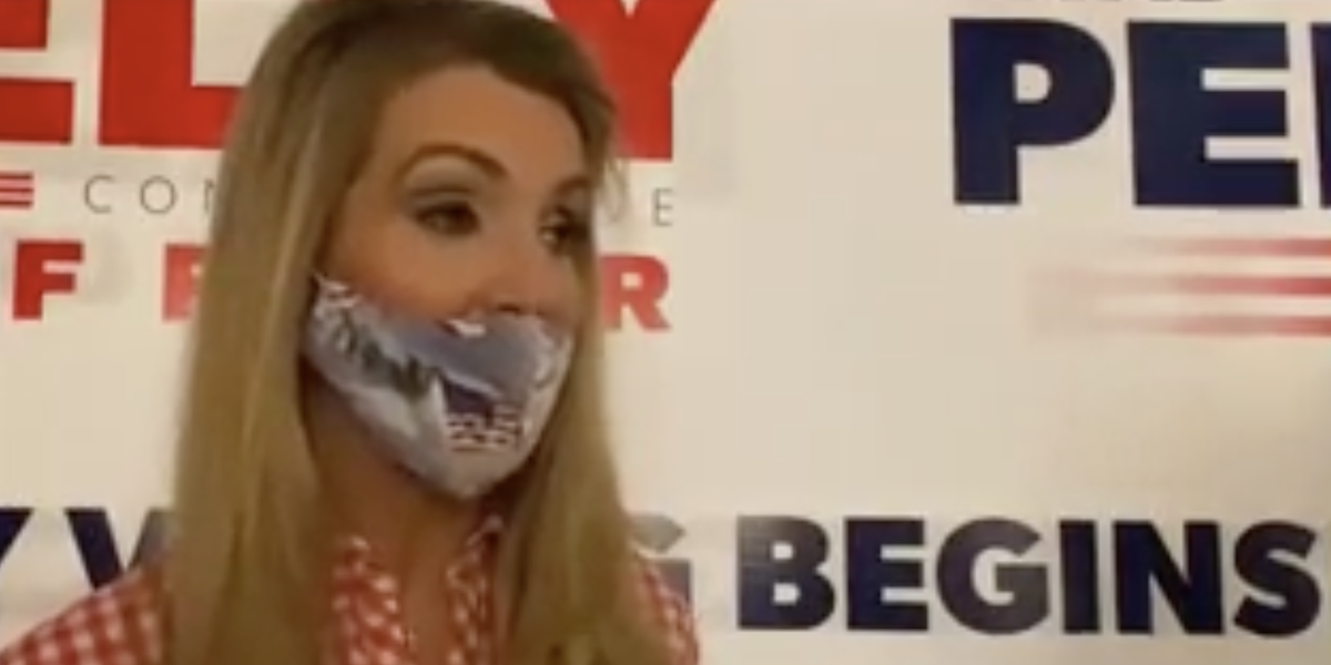 Kelly Loeffler wearing a mask and speaking to a reporter in front of a banner for her campaign