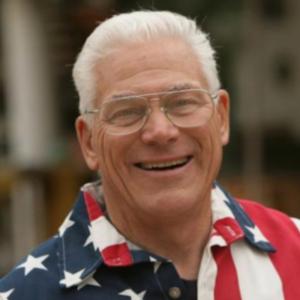 Robert Newman smiling headshot wearing an American flag polo shirt