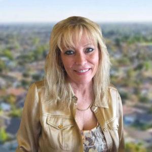 Rhonda Furin smiling in front of a blurred California neighborhood